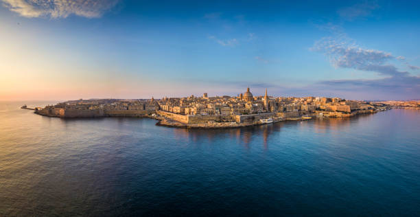Valletta, Malta - Aerial panoramic skyline of Valletta at sunrise with Our Lady of Mount Carmel church and St.Paul's Cathedral stock photo