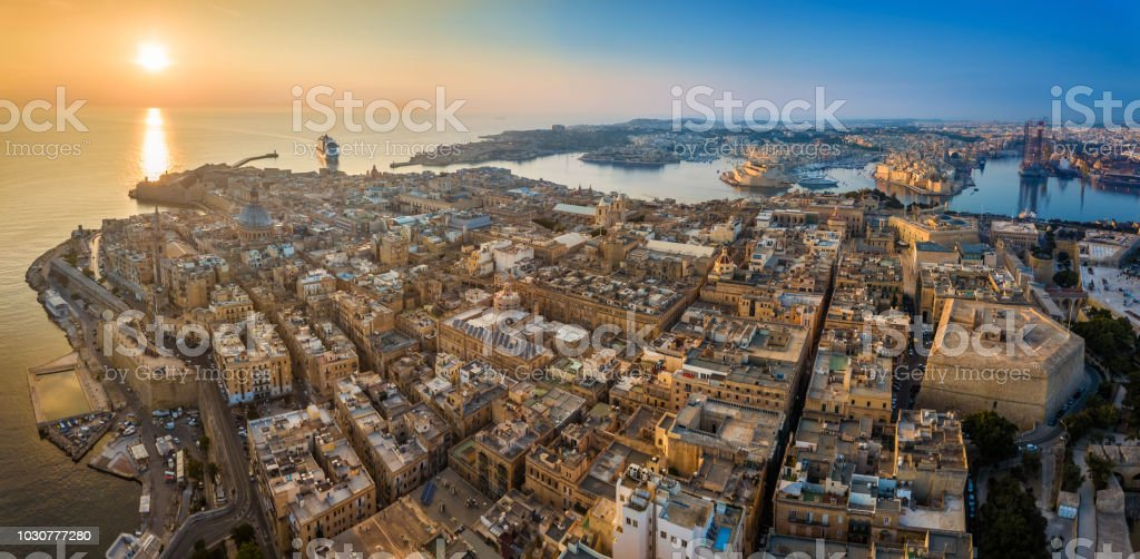 Valletta, Malta - Aerial panoramic skyline view of Valletta at sunrise with cruise ship entering at Grand Harbor stock photo