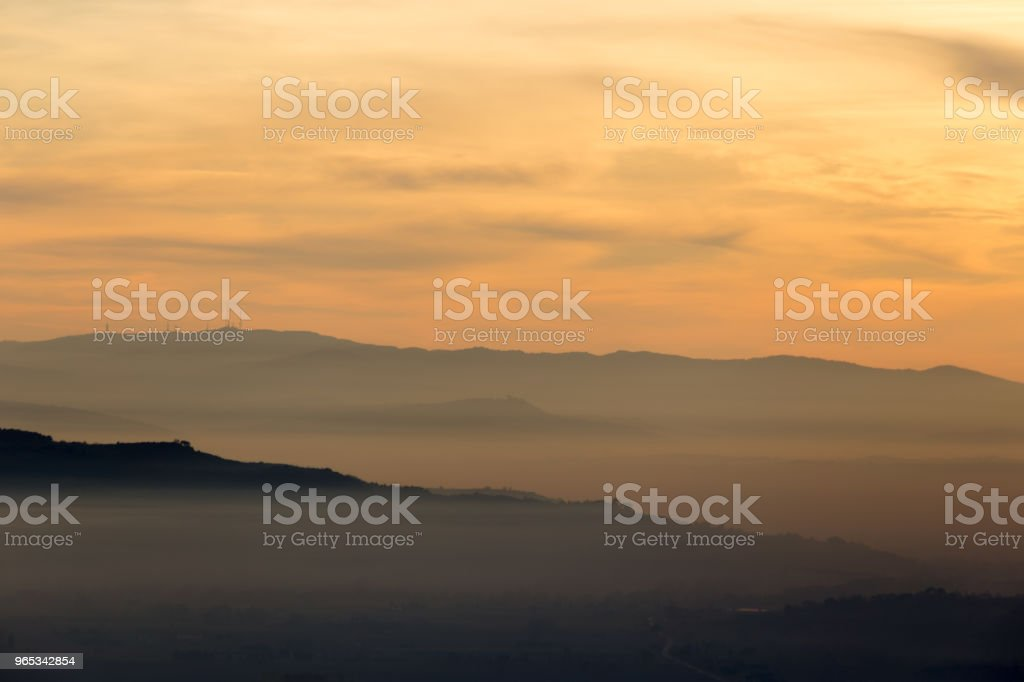 A valley filled by mist at sunset, with various layers of hills royalty-free stock photo