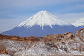 Valle de la Luna (Valley of the Moon) with the snowy Licancabur volcano in the background, the white in the foreground is salt, Atacama Desert, Chile
