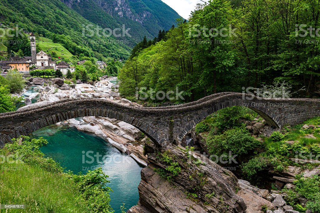 valley verzasca in Switzerland with old stone bridge and church stock photo