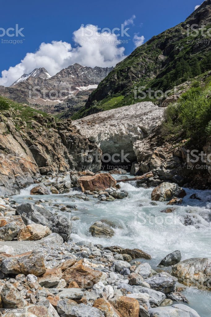 Valpelline, Aosta Valley, Italy. A stream flows under the remains of an avalanche near Prarayer stock photo