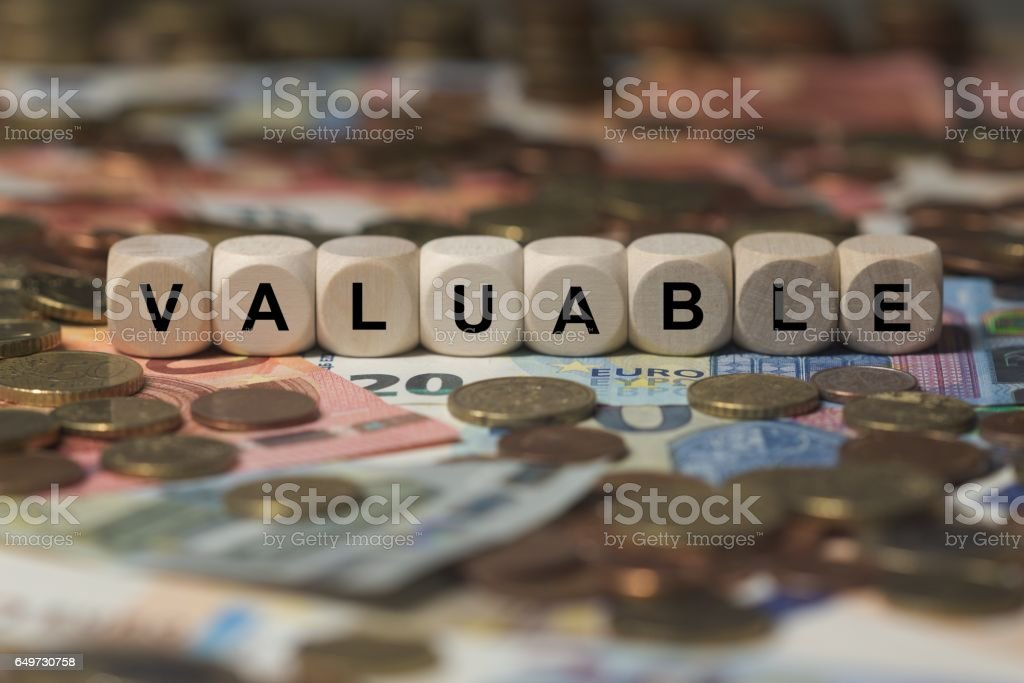 valuable - cube with letters, money sector terms - sign with wooden cubes stock photo