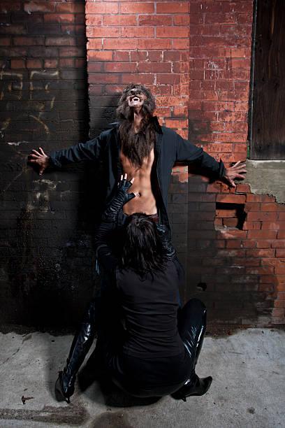 Vampire blowing a werewolf stock photo