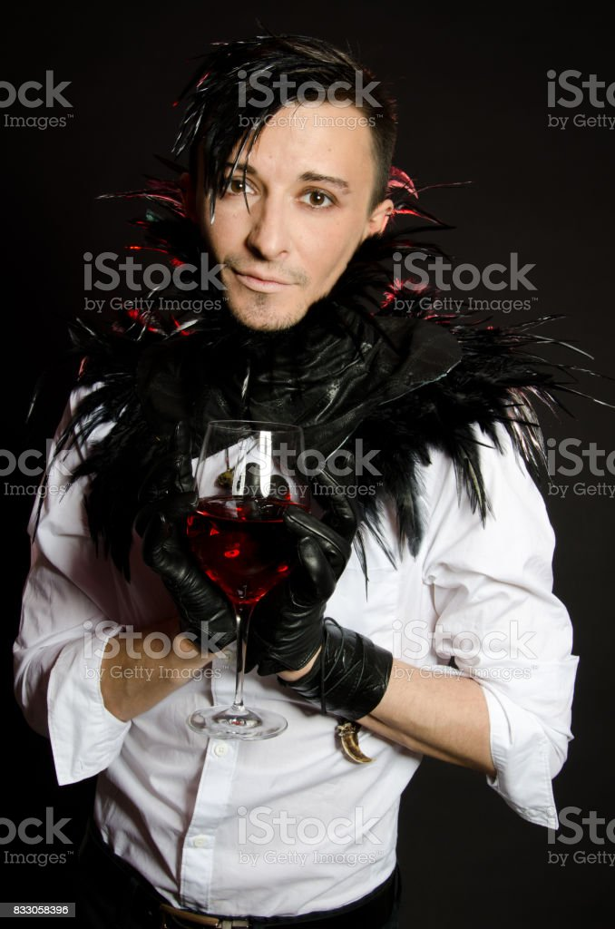 A vampire with a glass. Red wine or blood. stock photo