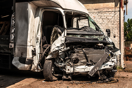 Destroyed white van after a frontal collision
