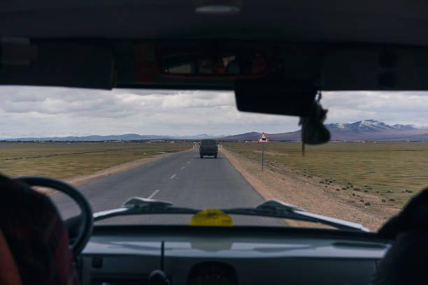 van on road through steppe at sunset - półpustynny zdjęcia i obrazy z banku zdjęć