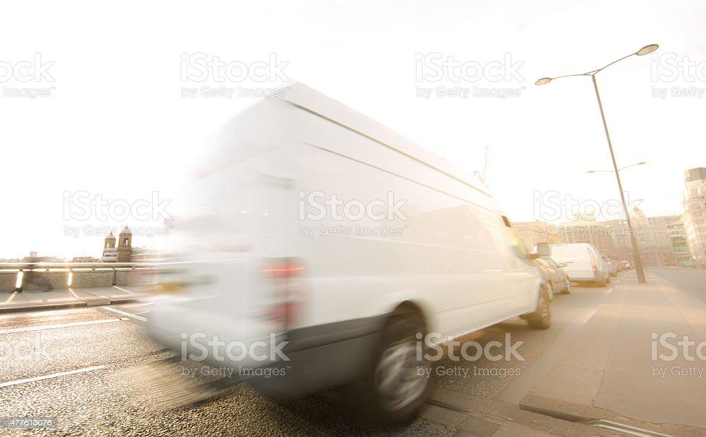van rushing through traffic stock photo