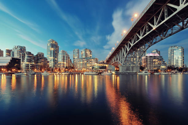 Vancouver False Creek Vancouver False Creek at night with bridge and boat. british columbia stock pictures, royalty-free photos & images