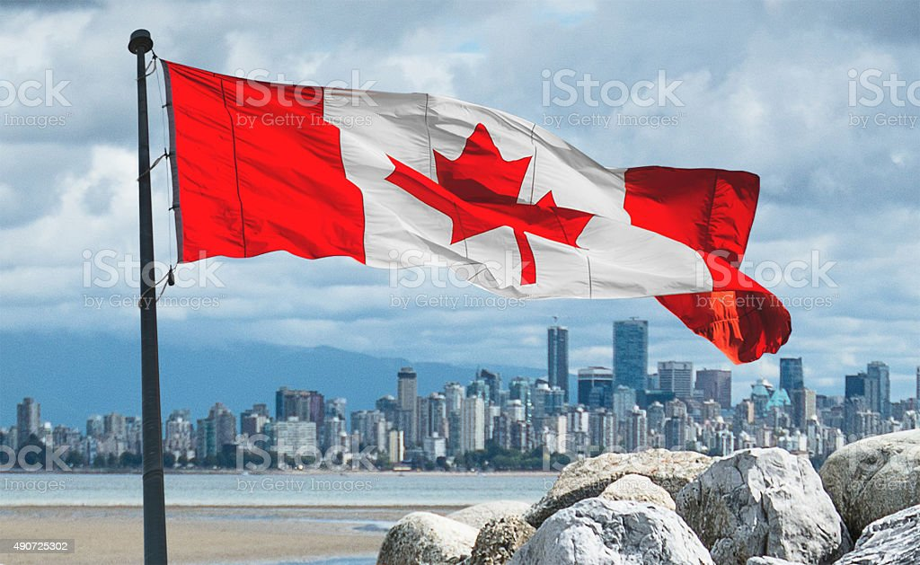 Vancouver skyline from the beach with canadian flag stock photo