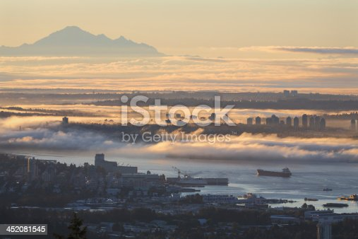 A high angle view of Vancouver and the Burrard Inlet at sunrise. Mount Baker, in Washington State, rises in the distance. British Columbia, Canada.