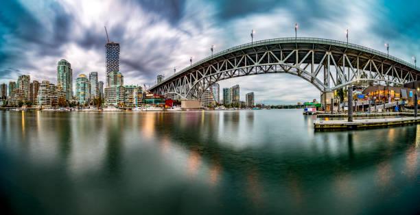 vancouver waterkant skyline met granville brug onder storm wolken - vancouver canada stockfoto's en -beelden