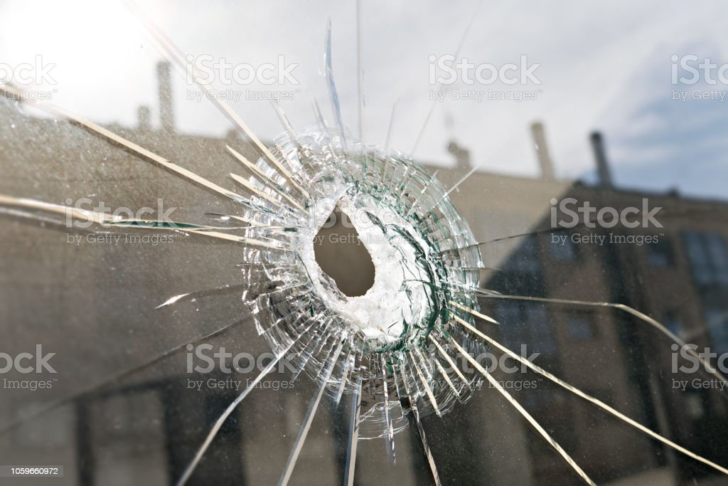 Vandalism or violence concept Broken glass with hole stock photo