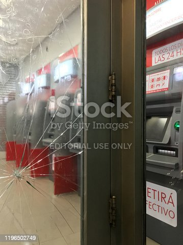 Buenos Aires, Argentina - December 24, 2019: Broken window of entrance door to ATM machines. This kind of vandalism though not frequent happens every once in a while all around the city