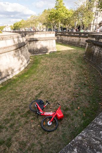 Paris, France - Sept 01, 2019: Vandalized Uber Jump electric bike thrown into the ditch of The Dome (tomb of Napoleon) - Musée de l'Armée