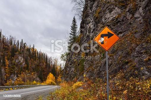 Vandalized road sign and autumn color along a rural road in the Talkeetna mountains in Alaska
