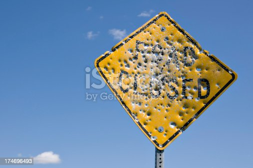 close up of vandalized road closed sign with many bullet holes against blue sky background