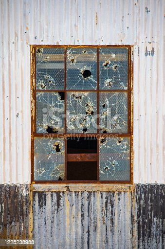 Vandalized window in old tin industrial building with holes from thrown rocks and or bullets in reinforced panes in rusty frame