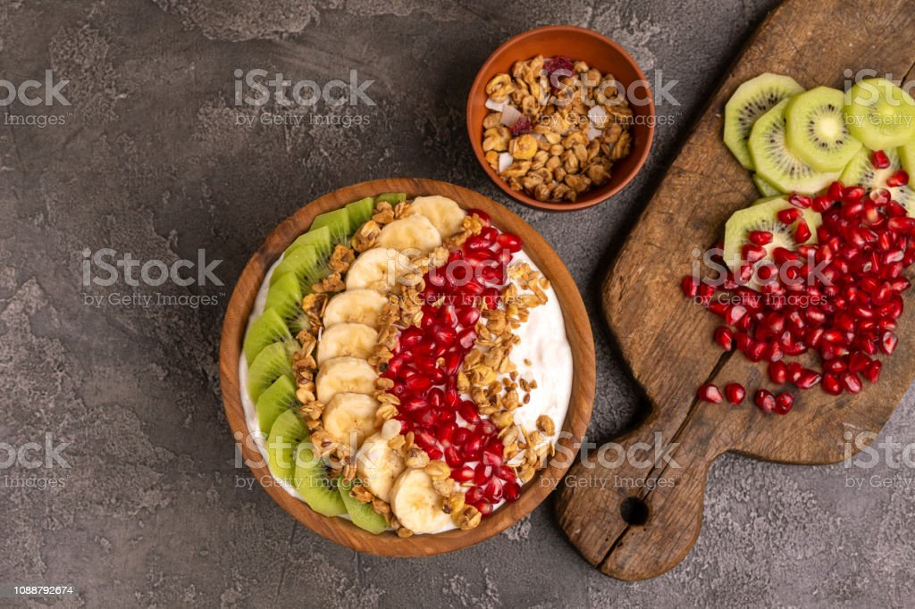 Vanille Acai Schüssel mit Kiwi, Banane, Granatapfel und Müsli mit Zutaten – Foto