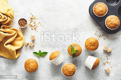 Vanilla Caramel Muffins In Paper Cups On Grey Concrete Background. Table Top View. Copy Space For Text