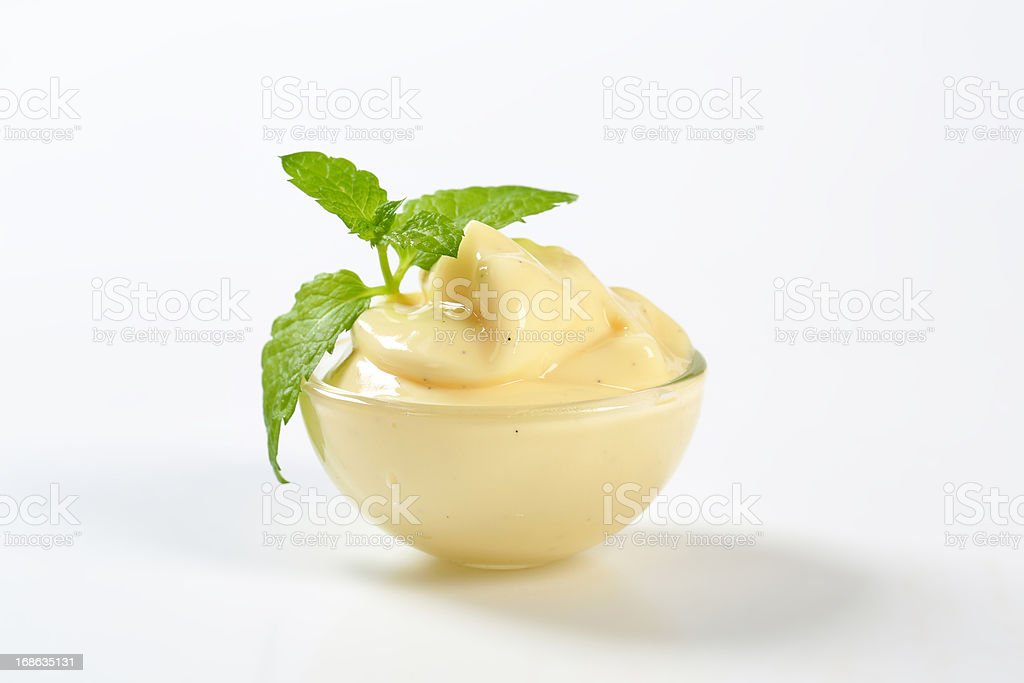 Vanilla cream in a bowl garnished by mint leaf stock photo