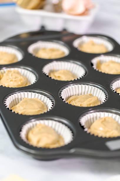 Vanilla cupcake batter in cupcake pan. Vanilla cupcake batter in cupcake pan. muffin tin stock pictures, royalty-free photos & images