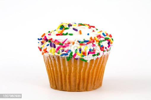 A vanilla and buttercream cupcake with sprinkles, isolated on white.