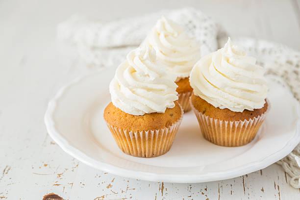 vanille cupcakes auf weiß holz-hintergrund - cupcake, zuckerguss stock-fotos und bilder
