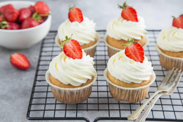 vanilla cupcakes with cream cheese frosting and fresh strawberry stock photo