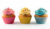 Studio shot of vanilla cupcakes with pink, yellow and blue frosting