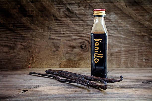l'extrait de vanille dans une bouteille sur bois rustique et bornes multimédias - vanille photos et images de collection