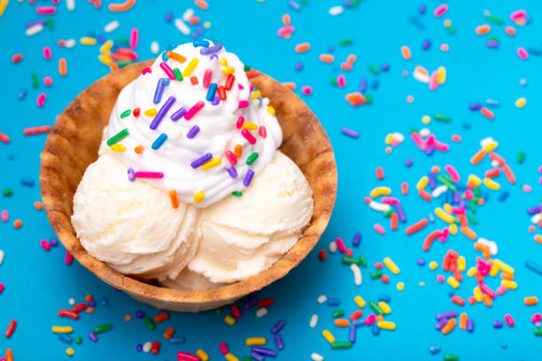 vanilla ice cream in a waffle cone bowl on a blue background - coppa gelato foto e immagini stock