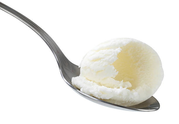 vanilla ice cream on a silver spoon over a white background - spoon stock photos and pictures