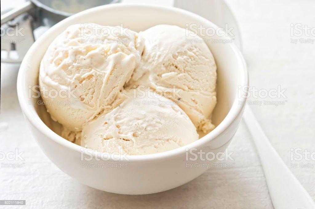 Vanilla ice cream scoops in white bowl stock photo