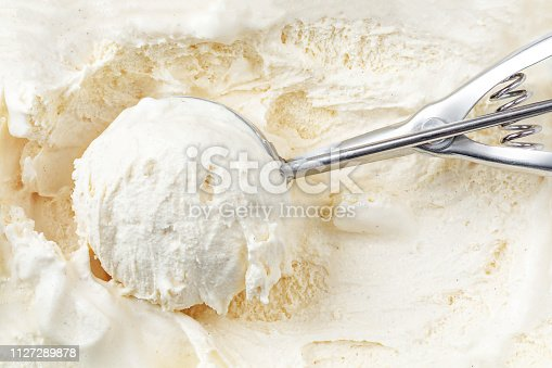 istock Vanilla ice cream with a scoop in  container as background. Macro. Scooped out ice-cream,  top view. 1127289878