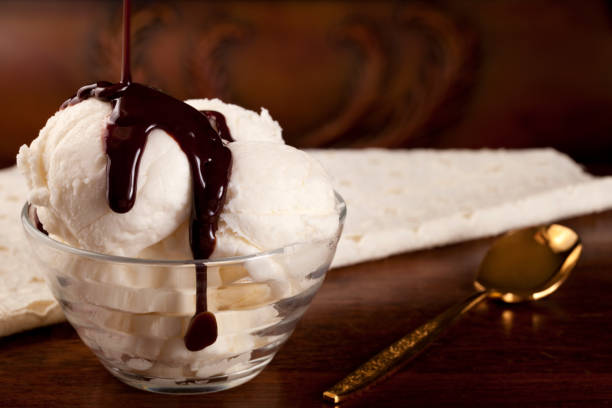 vanilla ice cream with chocolate syrup, gold spoon - chocolate syrup stock photos and pictures
