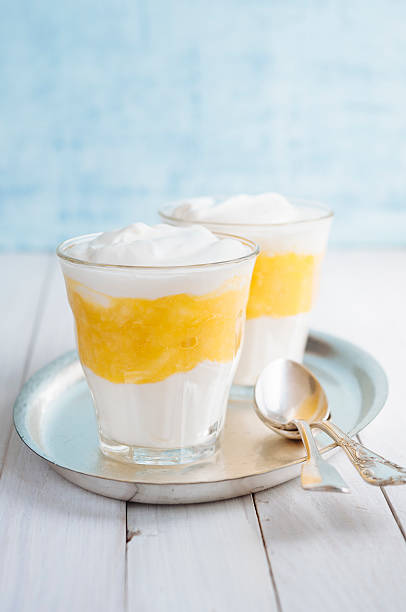 vanille-mango-dessert mit zwei löffel auf silver/tee-sortiment - dessert mit quark stock-fotos und bilder