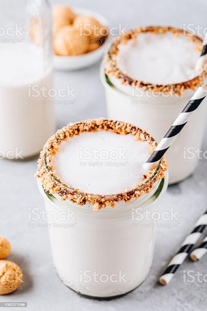 Vanilla milkshake with crispy cookies in glass mason jar on gray background stock photo