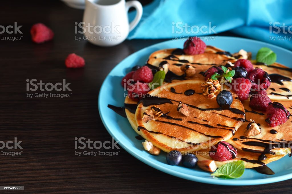 Vanilla pancakes with berries and chocolate sauce on a dark background photo libre de droits