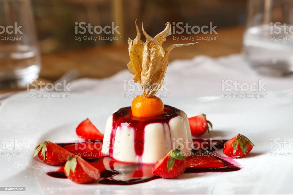 Vanille Pannacotta mit Erdbeeren und Physalis auf einem weißen Teller dekoriert. – Foto