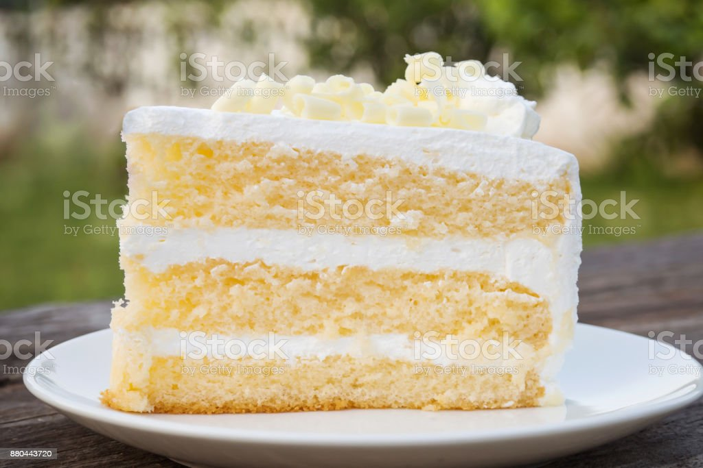 Vanilla sponge cake with cream and white chocolate decorate. Sliced piece of cake on white plate. Served on wooden table. - Стоковые фото Без людей роялти-фри