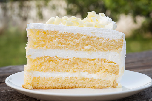 Vanilla Sponge Cake With Cream And White Chocolate Decorate Sliced Piece Of Cake On White Plate Served On Wooden Table — стоковые фотографии и другие картинки Без людей