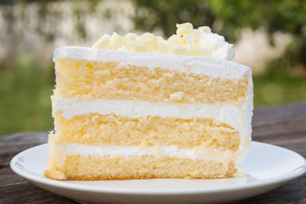 vanille spons cake met room en witte chocolade decoreren. gesneden fluitje van een cent op witte plaat. geserveerd op houten tafel. - gebak stockfoto's en -beelden