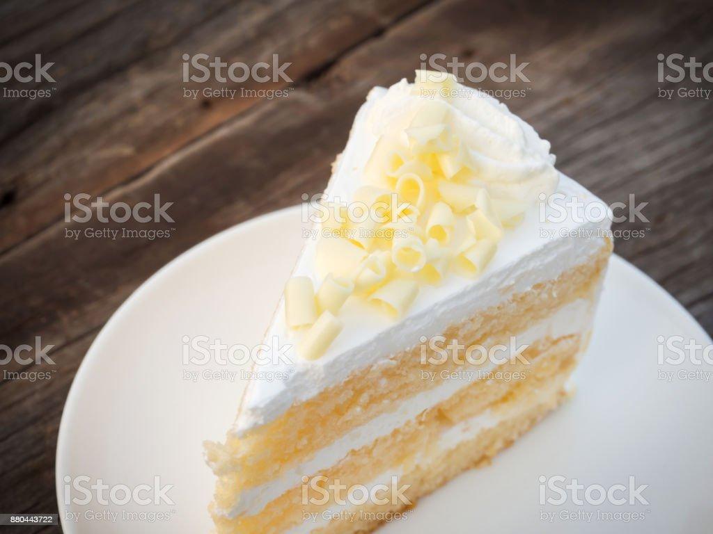 Vanille spons cake met room en witte chocolade decoreren. Gesneden fluitje van een cent op witte plaat. Geserveerd op houten tafel. foto
