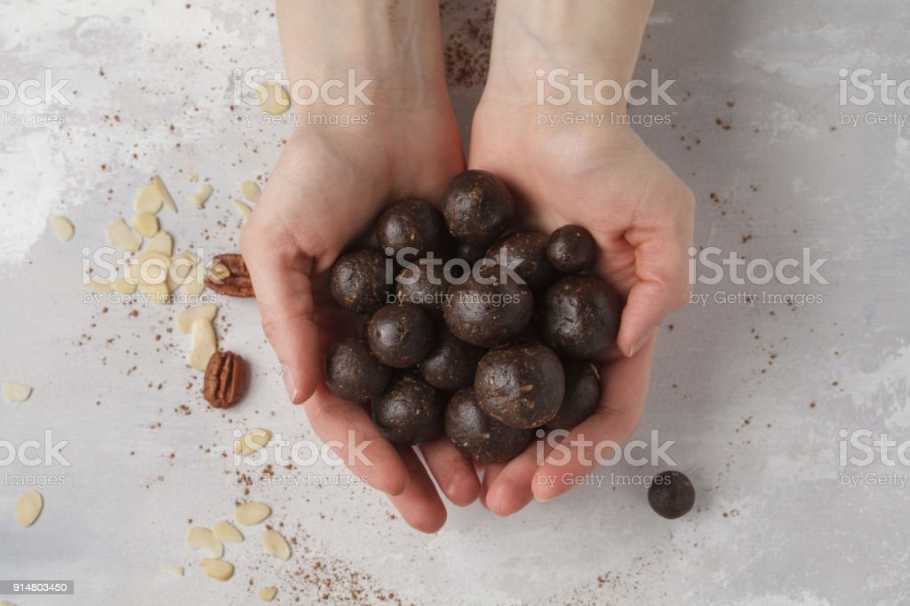 Vanilla-chocolate raw vegan sweet balls with nuts, dates and cocoa in hands. Healthy vegan food concept. Gray background stock photo