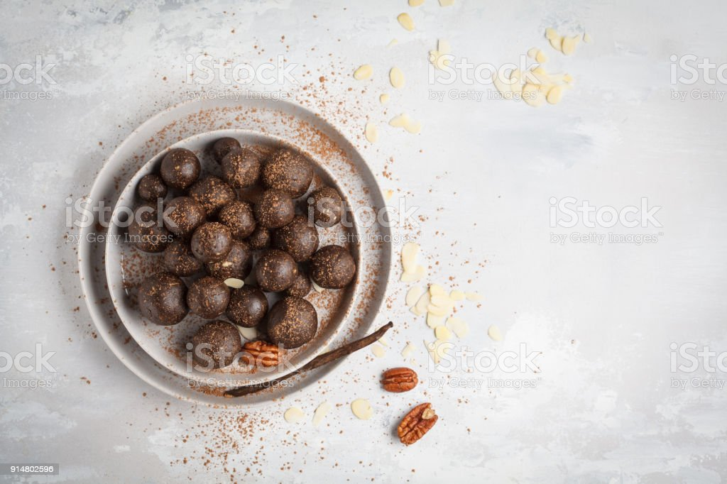 Vanilla-chocolate raw vegan sweet balls with nuts, dates and cocoa. Healthy vegan food concept. Gray background, top view, copy space stock photo
