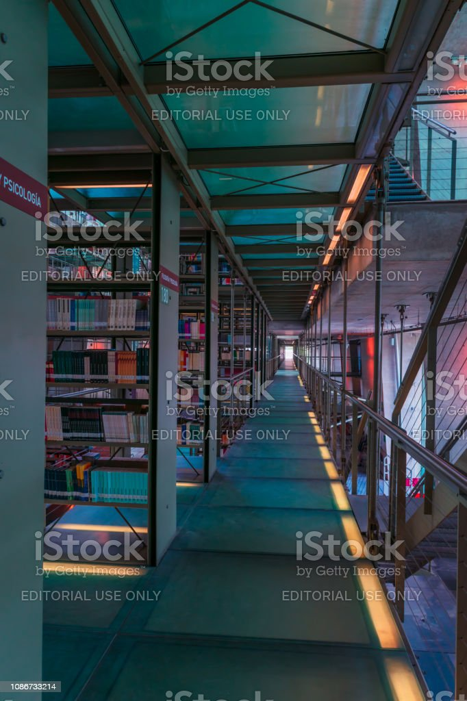 Vanishing point view of a large hall with shelfs full of books in the...