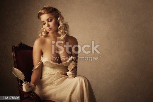 young woman looking at herself in the mirror & holding a hairbrush - vintage clothes, accessories, classic lighting, added brown tone, vignette, and real film grain for the mood