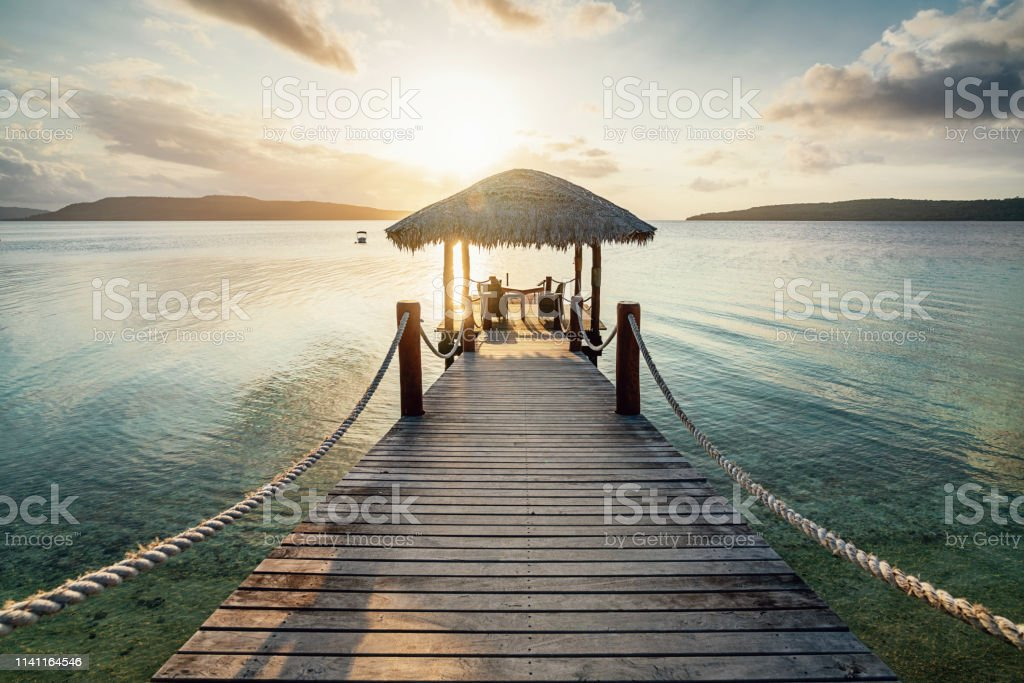 Vanuatu Romantic Sunset Jetty Efate Island Romantic vacations scene. Wooden jetty with table and lounge chairs towards the beautiful lagoon during sunset over Moso Island. Havannah, Efate Island, Vanuatu Beach Stock Photo