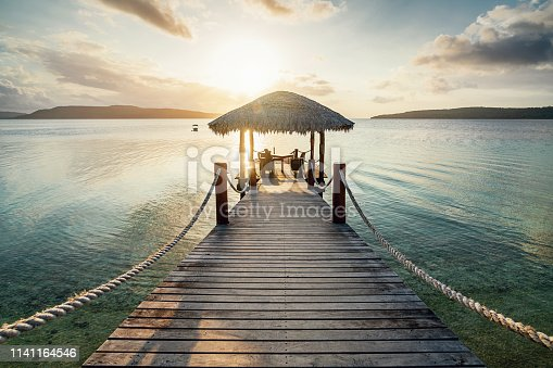Romantic vacations scene. Wooden jetty with table and lounge chairs towards the beautiful lagoon during sunset over Moso Island. Havannah, Efate Island, Vanuatu